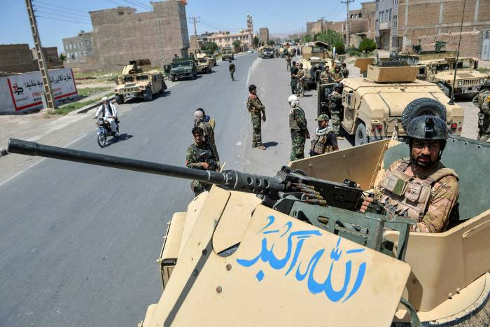 An Afghan army commando stands guards from on top of a vehicle in Herat province