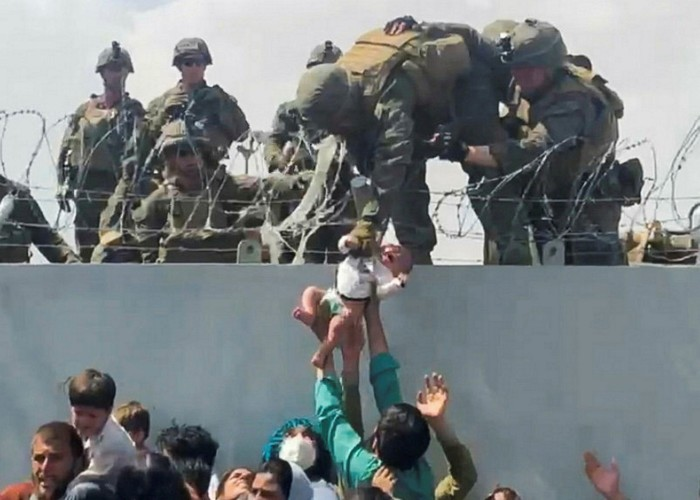 A baby is handed over to US soldiers over the perimeter wall of the airport for it to be evacuated, in Kabul