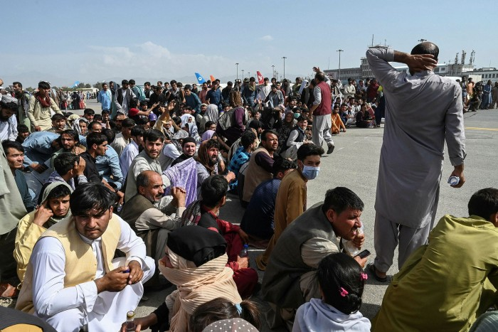 Afghan passengers sit as they wait to leave the international airport in Kabul on August 16