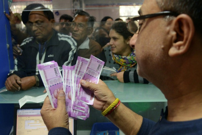 An Indian bank teller counts out notes as senior citizens wait to withdraw money at a bank in Amritsar, India