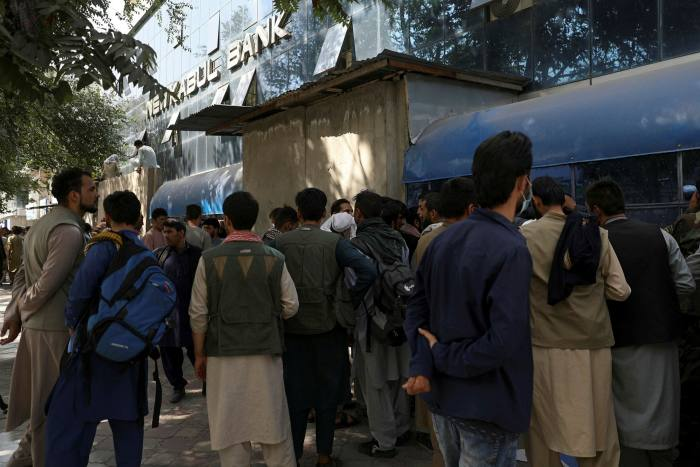 Afghans wait in long lines for hours to try to withdraw money, in front of a bank branch in  Kabul in the hours ahead of the Taliban's arrival in the capital