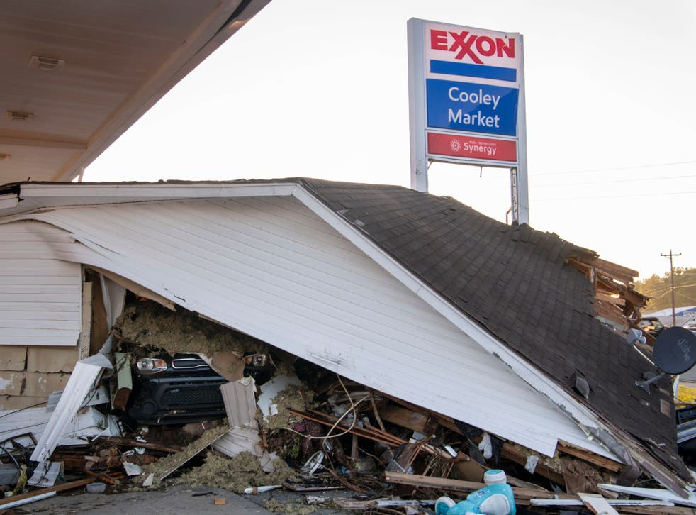 <p>A car peeks out from under a house that was destroyed by floodwaters at the Cooley Market in Waverly, Tennessee</p>